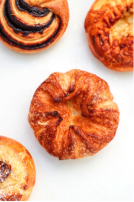 KOUIGN-AMANN- Our Signature item! The Kouign-Amann is a Bretton pastry that's similar to croissants but with a lot more butter and sugar to give a caramelizing effect. It's all about the crunch!
